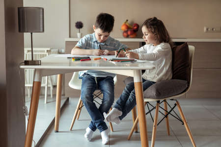 Little happy brother and sister sitting at a table at home in the kitchen and drawing a picture with colored pencils and markers Reklamní fotografie