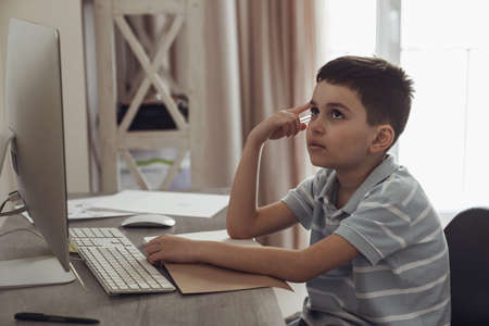 Little boy sitting in his room at a desk next to a computer and doing homework preparing for school