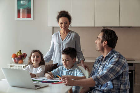 Mom helps little daughter and son draw while father works at home with computer and documents sitting at table in kitchen and smiling looking towards his wife Reklamní fotografie