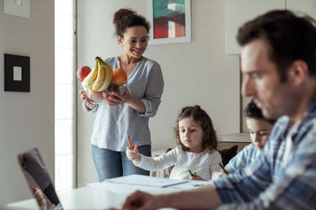 Mom treats father to fruit while working at home with a computer and documents sitting at a table in the kitchen and their little daughter and son who draw with colored pencils and markers
