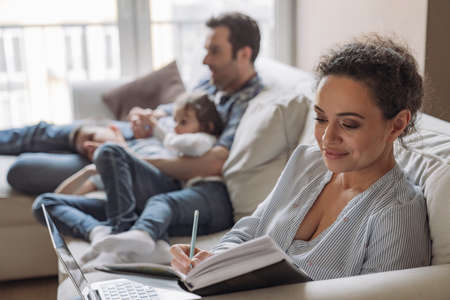 Young successful freelancer woman working at home sitting on sofa against the background of her husband and young son and daughter who are watching TV and having fun
