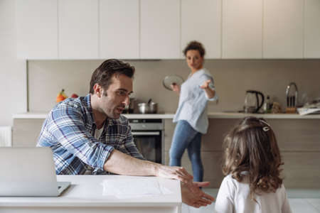 Young freelancer man working at home with computer and documents with his daughter sitting at a table in the kitchen against the backdrop of his wife preparing food
