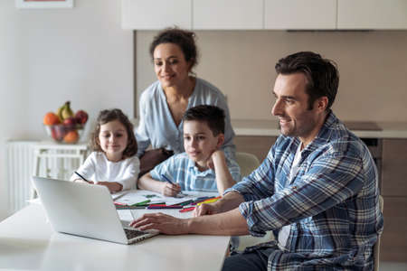 Mom helps little daughter and son draw while father works at home with computer and documents sitting at table in kitchen