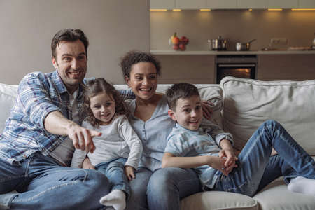 Young cheerful family where dad, mom, and little son and daughter sitting on sofa and smiling watching tv at home
