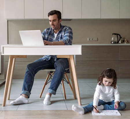 Dad works at home with computer and documents sitting at a table in the kitchen and his little daughter who draws with colored pencils and markers sitting on the floor