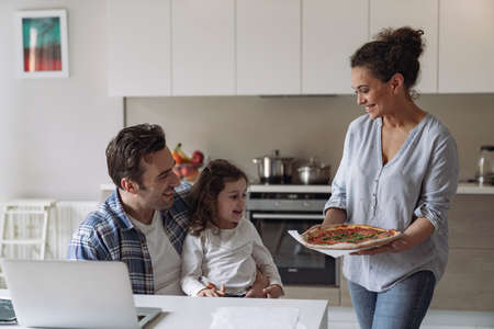 Young woman makes pizza and treats her husband to a freelancer working at home with a computer and documents with her little daughter sitting at a table in the kitchen Reklamní fotografie