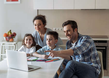 Mom helps little daughter and son to draw while father works at home with computer and documents sitting at the table in the kitchen and points his hand towards his computer