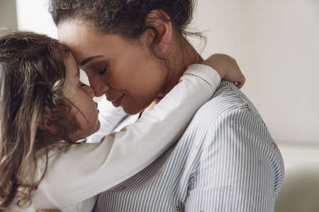 Good family, mother and daughter. Little daughter hugging her mother with a smile and closed eyes at home