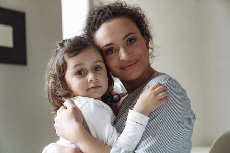 Good family, mother and daughter. Little daughter hugging her mom with a smile looking at the camera at home