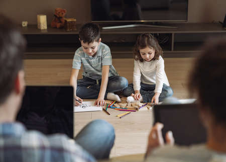 Little boy and girl play and draw sitting on the floor against the backdrop of their dad and mom working at home sitting on sofa with laptop and tablet