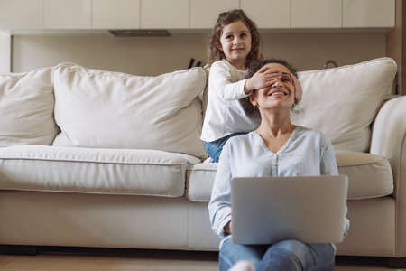 Young successful female freelancer while working at home with laptop and documents sitting on the floor near the sofa and behind her little daughter closes her mother's eyes