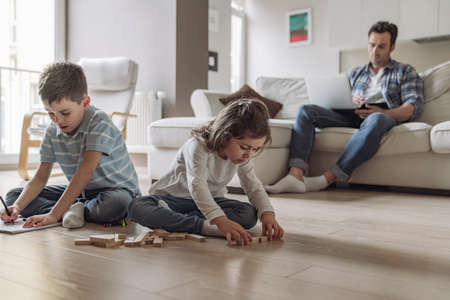 Little boy and girl play and draw while sitting on the floor on the background of their father who works at home sitting on the couch with a laptop
