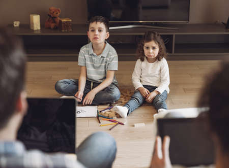 Little boy and girl play and draw sitting on the floor against the backdrop of their dad and mom working at home sitting on the couch with laptop and tablet. Children want attention from their parents.
