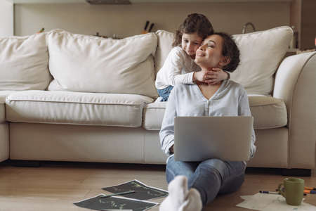 Young successful freelancer woman while working at home with laptop and documents sitting on the floor near the sofa and behind her little daughter hugs mom around the neck Reklamní fotografie