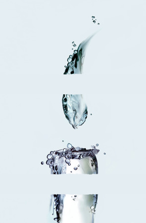 A lighted blue water candle sliced into four parts. Archivio Fotografico