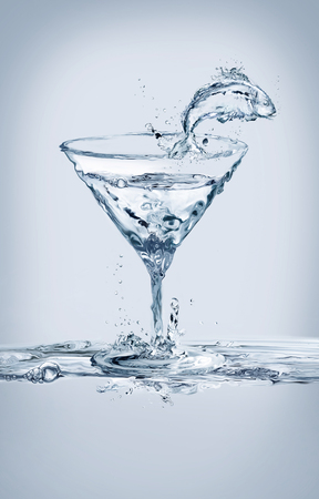 A fish jumping out glass of a martini glass made of water.