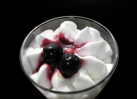 A frozen yogurt and cream glass filled with vanilla topped with black cherries.