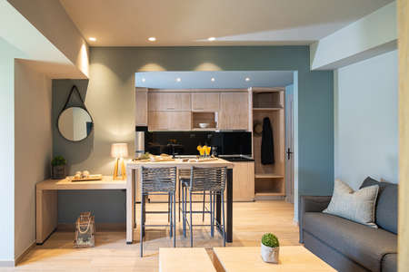 Modern grey and wooden interior of small studio apartment. Front view of hotel flat room witn kitchen, living, bedroom in single space Фото со стока