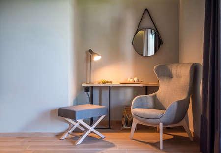 Interior moderno de habitación gris con sillón orejero. Fondo de estilo escandinavo con espacio de copia de pared vacía