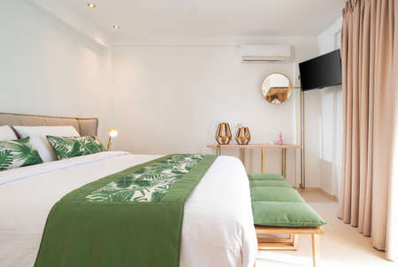 Modern ecological style interior of hotel room with empty wall copy space. Side view of white bedroom with green palm leaves bedding