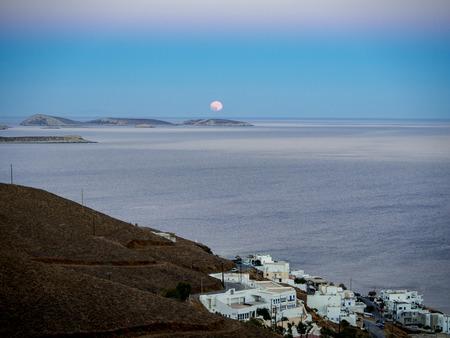 Τhe moonrise shortly after sunset with some white traditional houses in the front ground