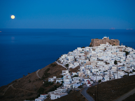 A lithe road leading to Chora of Astypalaia in blue hour and the full moon rising from the horizon