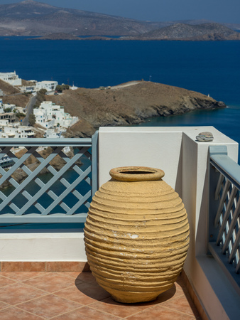 Î' large clay pot on the balcony near the wooden blue fence overlooking the blue sea of aegean Banco de Imagens