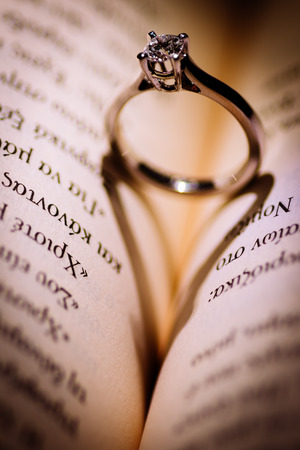 An engagement ring that forms a heart with his shadow on a book Stock Photo