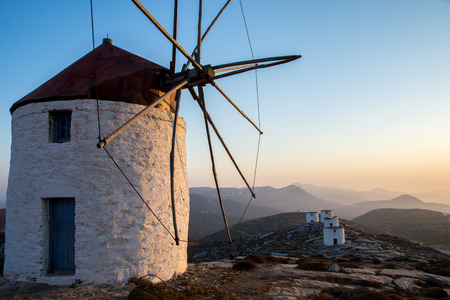 A windmill at the top of the Chora of Amorgos with a series of deserted windmills at the background