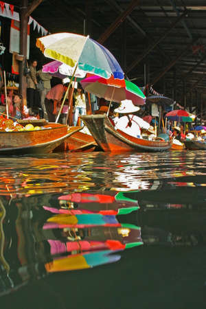 saduak: Boats reflecting in the water, Floating market Damnoen Saduak, near Bangkok, Thailand