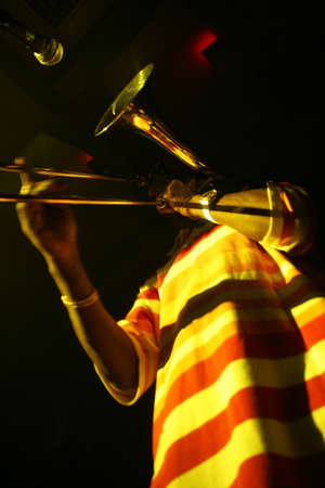 trombon: Un hombre que toca el tromb�n, vista desde abajo, ilusi�n �ptica - tromb�n en lugar de la cabeza