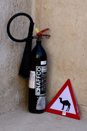 Black fire extinguisher and a camel road sign photo