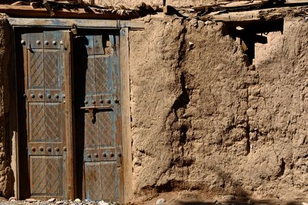 mud house: Old peeled blue door on a willage mud house in Oman Stock Photo