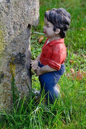 garden gnome: Little boy garden gnome standing next to a tree Stock Photo