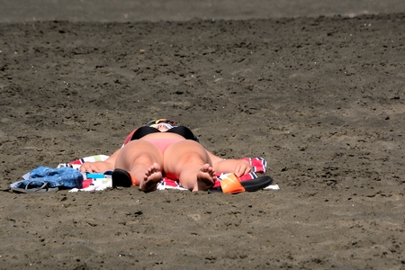 newzealand: A single lady sunbathing at Piha beach New Zealand in the summer time on the black sand. Stock Photo