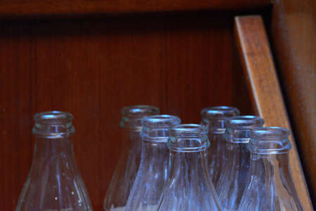top 7: Seven glass bottles in front of a wooden wall