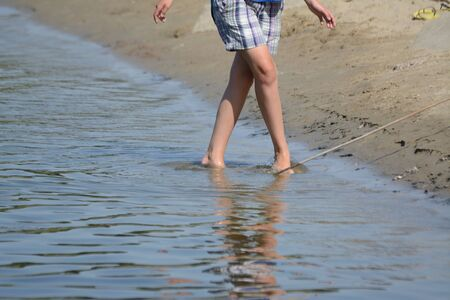 White women legs walking in the water at the beach