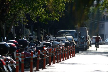 Long row of motorcycles on the street on the sun