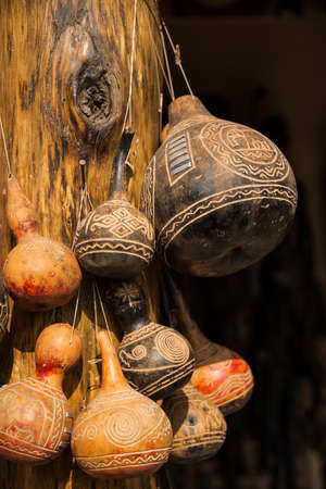 Carved decorative African gourds for holding water hanging on post in Tanzania, Africa