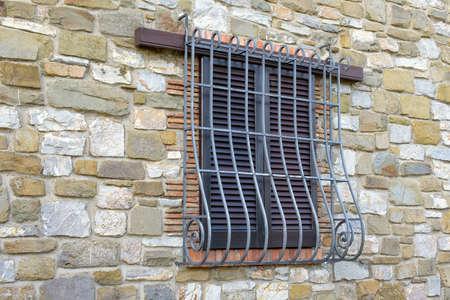 ventana con reja de hierro en la pared de piedra