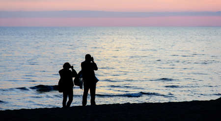 couple silhouette photographing the sunset on the beach