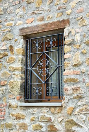 janela com grade de ferro na parede de pedra