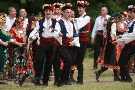Varvara, Bulgaria - May 5, 2015: People in traditional costumes dance bulgarian horo a meadow near the village of Varvara