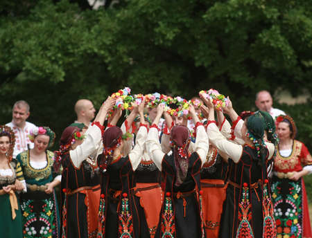 Varvara, Bulgaria - May 5, 2015: People in traditional costumes dance bulgarian horo a meadow near the village of Varvara