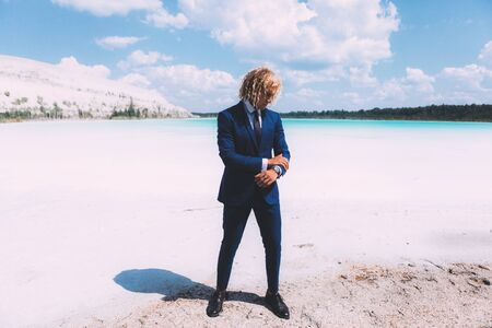 Portrait of blond curly man dressed blue business suit. Clear water and blue sky on the background. Summer time. Travel topic