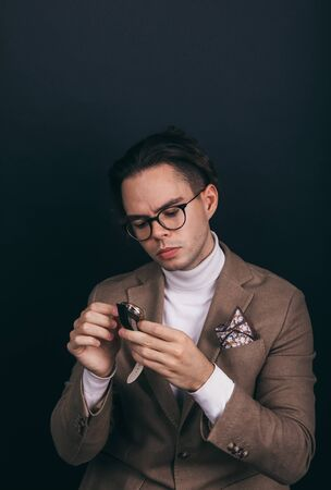 A dapper young man wearing a white turtleneck sweater and a beige jacket with handkerchief in his top breast pocket Stock fotó