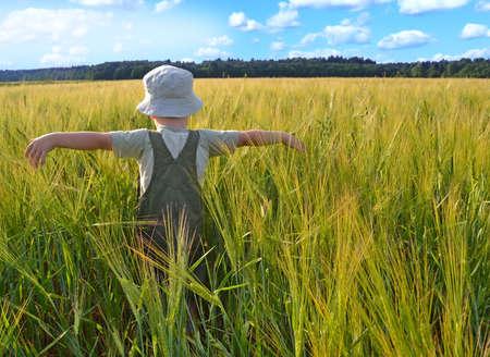 Retrato de un niño de pie en un campo de trigo