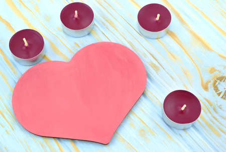 Image of pink heart and candles on light blue background photo