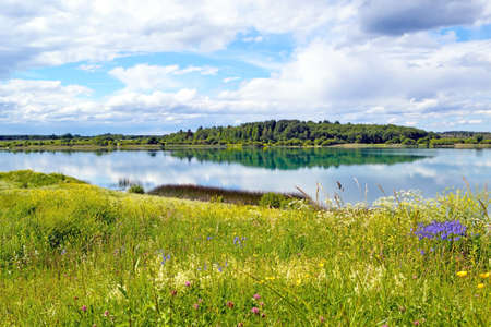 Landscape which shows the blue lake with grass and sky with clouds and forest photo