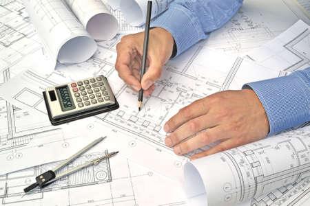 Handen van ingenieur werken met het gereedschap op project tekeningen achtergrond